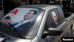 FILE - A poster of Syria's President Bashar al-Assad and a photo of Russian President Vladimir Putin, right, are seen on a car near Latakia, Syria, May 26, 2014.