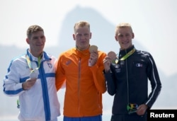 Gold medalist Ferry Weertman (NED) of the Netherlands, silver medalist Spiros Gianniotis (GRE) of Greece (L) and bronze medalist Marc-Antoine Olivier (FRA) of France (R) pose with their medals for Men's 10km Marathon Swimming, Rio de Janeiro, Aug. 16, 2016.