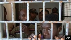 FILE - African migrants look through bars of a locked door at Sabratha migrant detention center for men in Sabratha, Libya, October 2013.