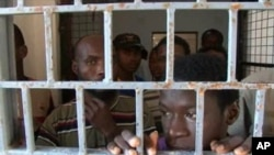 FILE - African migrants look through bars of a locked door at Sabratha migrant detention center for men in Sabratha, Libya, Oct. 2013.