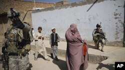 An Afghan woman walks among U.S. soldiers from on patrol in Kandahar City, Afghanistan, Oct. 22, 2010.