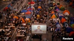 Pro-democracy protestors watch formal talks between student protest leaders and city officials on a video screen near the government headquarters in Hong Kong, Oct. 21, 2014.