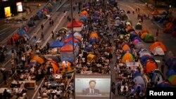 示威者在香港政府總部附近觀看學聯代表與港府官員對話的直播