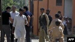 Pakistanska policija posmatra novinare pored kuće Osame bin Ladena u Abotabadu