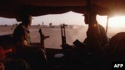 """Des soldats maliens se dirigent à bord de camions vers un lieu de manoeuvres, le 27 février à Kidira, dans le cadre de l'exercice """"Guidimakha 98"""" associant les armées française, britannique, américaine et sénégalaise."""