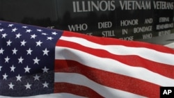 A United States flag blows in the wind near the Illinois Vietnam Memorial, July 3, 2012, in Springfield, Ill.