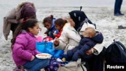 难民们在德国慕尼黑一个临时搭建的难民营外进食(2015年9月7日)