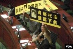 兩名人民力量立法會議員在答問大會上高舉標語,要求梁振英下台