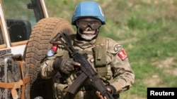 FILE - A United Nations peacekeeping soldier provides security during a food aid delivery by the United Nations Office for the Coordination of Humanitarian Affairs and world food program in the village of Makunzi Wali, Central African Republic, April 27.