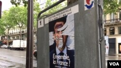 This campaign poster, like many others in Paris, was defaced, May 6, 2017. France's election has been marked by dissatisfaction with both candidates and deep anti-establishment sentiments. (Photo: L. Ramirez/VOA)