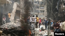 People inspect the damage at a site hit by airstrikes, in the rebel-held area of Aleppo's Bustan al-Qasr, Syria April 28, 2016.