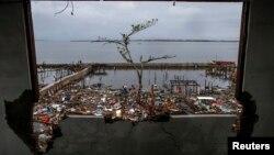 從遭到海燕颱風破壞的建築物向外望﹐一名災民拿著救援物資走在破爛的路上。