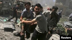 Men transport a casualty after airstrikes by Assad regime near Damascus, Syria. (File)