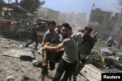 FILE - Men transport a casualty after what activists said were airstrikes by forces loyal to Syria's President Bashar al-Assad on a busy marketplace in Douma, near Damascus, Syria, Aug. 12, 2015.