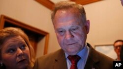 FILE - Republican U.S. Senate candidate Roy Moore, center, looks at election returns with staff during an election-night watch party, Dec. 12, 2017, in Montgomery, Alabama.