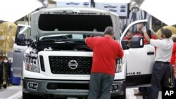 FILE - Technicians make final inspections to vehicles on an assembly line at the Nissan Canton Assembly Plant, in Canton, Mississippi, March 19, 2018.