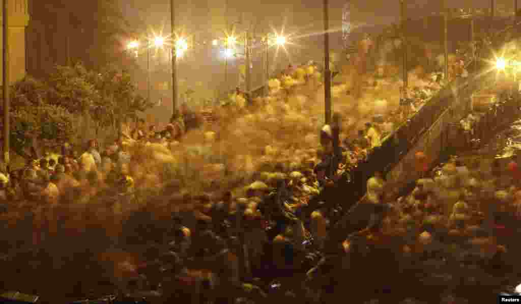 Supporters of Mohamed Morsi run from tear gas fired by riot police during clashes on the Sixth of October Bridge in central Cairo, July 15, 2013.