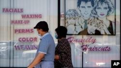 Sepasang suami-istri mengenakan masker melintas di depan salon kecantikan yang tutup akibat wabah virus corona (Covid-19) di Panorama City, Los Angeles, 14 Juli 2020.