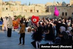 Anak-anak Palestina bermain saat sholat Idulfitri, di kompleks yang menampung masjid al-Aqsa, yang dikenal oleh Muslim sebagai Tempat Suci dan Orang Yahudi sebagai Temple Mount, di Kota Tua Yerusalem , di tengah pertempuran Israel-Gaza 13 Mei 2021.