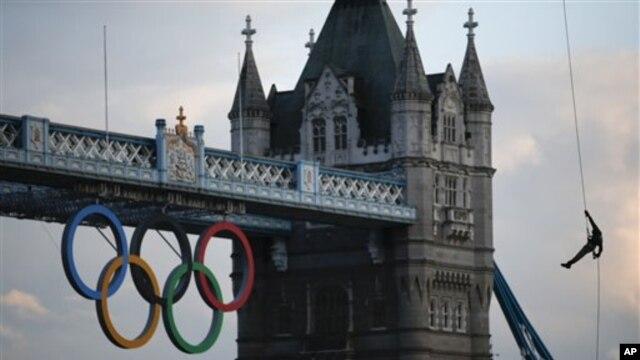 Sĩ quan Hải quân Hoàng gia Anh Martyn Williams (bên phải) cầm chiếc đuốc Olympic, đu dây từ máy bay trực thăng Sea King xuống Cầu Tower of London, ngày 20/7/2012.