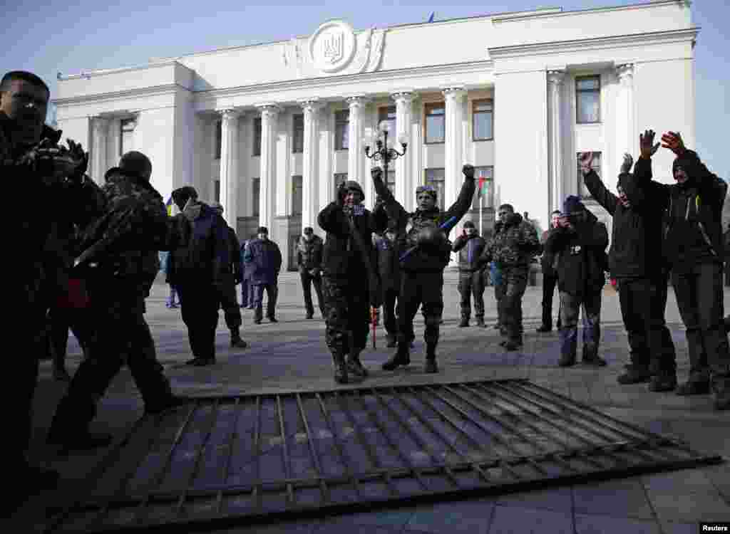 Members of self-defense units react after demolishing a fence enclosing the parliament building in Kyiv, Feb. 26, 2014.