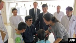 Blind activist Chen Guangcheng speaks with his wife Yuan Weijing and children as U.S. ambassador to China Gary Locke.
