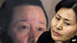 Geng He, wife of disappeared Chinese human rights lawyer Gao Zhisheng, seen on poster at rear, is interviewed before a news conference with Rep. Chris Smith, R-N.J., on Capitol Hill in Washington, Jan. 18, 2011, where he called attention to human rights
