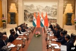 FILE - In this photo released by the Indian Ministry of External Affairs, Indian Prime Minister Narendra Modi, center left, and Chinese President Xi Jinping, center right, sit with delegation members for a meeting in Wuhan, China, Friday, April 27, 2018.