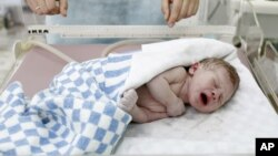 An infant boy cries shortly after mother Alla Baturina gave birth to him, at a perinatal centre of Moscow City Hospital Number 8 in Moscow October 31, 2011. The world's population will reach seven billion on Monday, according to projections by the United