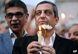 Yehia Qalash, the head of the journalists' union, holds a candle during a candlelight vigil for the victims of EgyptAir flight 804 in front of the Journalists' Syndicate in Cairo, May 24, 2016.