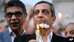 FILE - Yehia Qalash, the head of the journalists' union, holds a candle during a candlelight vigil for the victims of EgyptAir flight 804 in front of the Journalists' Syndicate in Cairo, May 24, 2016.