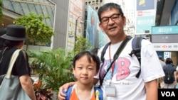 香港市民蘇先生帶同8歲兒子參與7-1大遊行 (美國之音特約記者 湯惠芸拍攝)