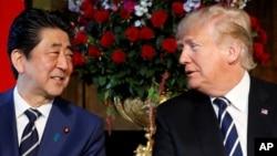 El presidente Donald Trump (derecha) y el primer ministro japonés Shinzo Abe, conversan durante una reunión en Mar-a-Lago, la mansión del mandatario estadounidense en Palm Beach, Florida. Abril 17 de 2018.