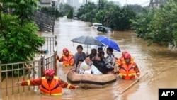 Tim penyelamat mengevakuasi warga yang terkena dampak banjir setelah hujan lebat di Jiujiang di provinsi Jiangxi di China, 8 Juli 2020. (Foto oleh STR / AFP) / China OUT