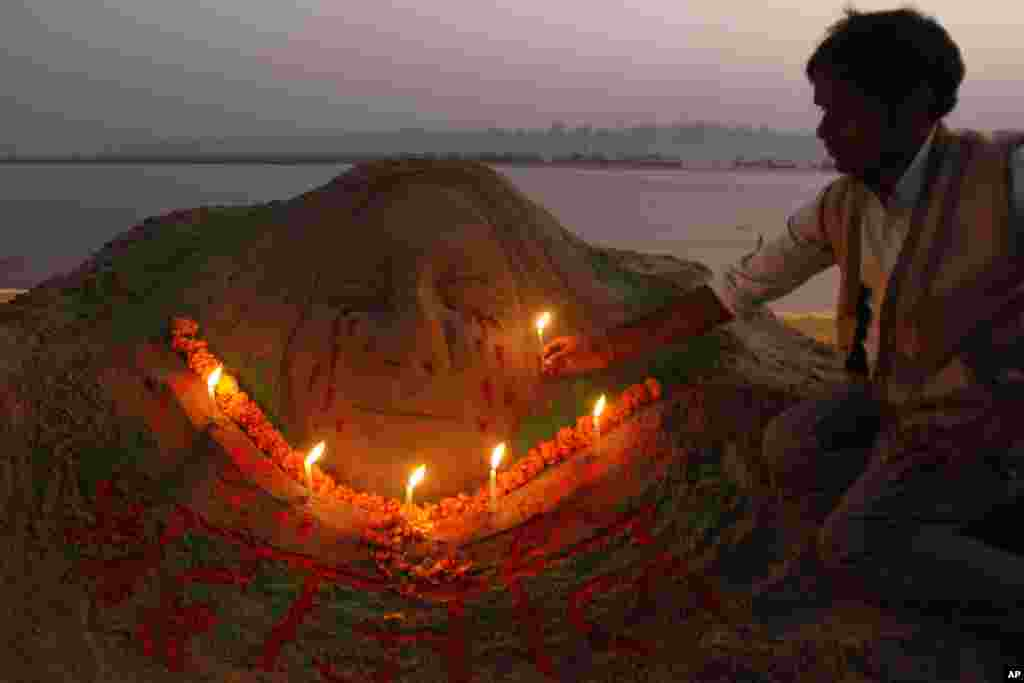 Sand artist Raj Kapoor holds a candle near a sculpture at the Sangam to pay tribute to a gang rape victim who died early Saturday, in Allahabad, Saturday, Dec. 29, 2012.