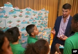 FILE - Colgate global ambassador Michael Phelps speaks to students in Celebration of Campus Sustainability Month at Alain L. Locke Magnet School, Oct. 19, 2017, in New York.