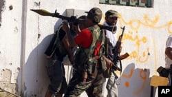 一名利比亚发政府武装的战士8月24日在的黎波里准备向忠于卡扎菲的狙击手据点发射火箭推进榴弹