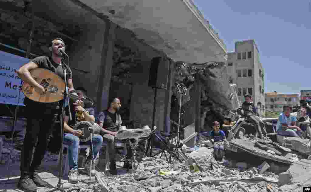 Members of the Palestinian band Dawaween perform on the remains of a building that was recently destroyed by Israeli airstrikes, in Gaza City, during a musical event calling for a boycott of the Eurovision Song Contest, hosted by Israel.