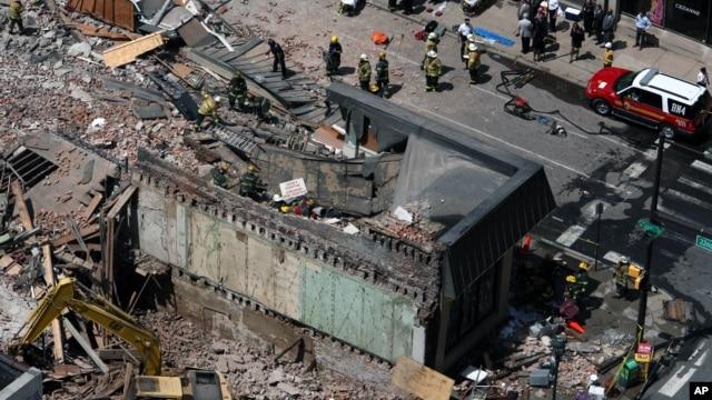 Rescue personnel search the scene of a building collapse in downtown Philadelphia, Pennsylvania, June 5, 2013.
