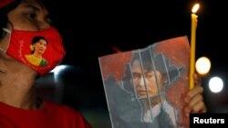 រូបឯកសារ៖ ពលករចំណាកស្រុកមីយ៉ាន់ម៉ាម្នាក់កាន់រូបលោកស្រី Aung San Suu Kyi ក្នុងពេលធ្វើបាតុកម្មប្រឆាំងនឹងរដ្ឋប្រហារយោធានៅក្នុងប្រទេសមីយ៉ាន់ម៉ា នៅទីក្រុងបាងកក ប្រទេសថៃ កាលពីថ្ងៃទី៦ ខែកុម្ភៈ ឆ្នាំ២០២១។