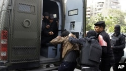 Egyptian security forces detain a man during clashes with supporters of ousted President Mohamed Morsi in the Nasr City neighborhood of Cairo, Egypt, Friday, Jan. 17, 2014.