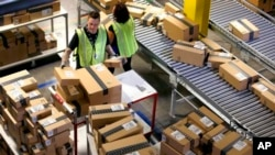 """In this file photo, Amazon employees organize outbound packages at an Amazon.com Fulfillment Center on """"Cyber Monday."""" Amazon has dropped some shoppers who returned too many purchases. (AP Photo/Ross D. Franklin)"""