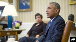 Attorney General Loretta Lynch listens as President Barack Obama speaks in the Oval Office of the White House in Washington, Jan. 4, 2016, during a meeting with law enforcement officials to discuss actions the president can take to curb gun violence in the U.S.