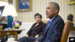4일 바락 오바마 미국 대통령이 백아관 집무실에서 로레타 린치 법무장관(뒤) 등과 만나 총기 규제 권고안과 관련해 대화하고 있다.