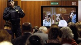 A bailiff stands in a room as people watch a live broadcast of a court hearing on members of the female punk band 'Pussy Riot' in Moscow October 10, 2012.