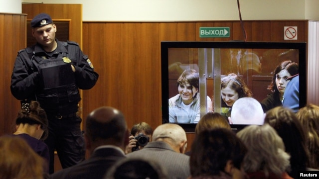 A bailiff stands in a room as people watch a live broadcast of a court hearing on members of the female punk band Pussy Riot in Moscow, October 10, 2012.
