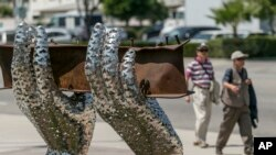 "Pedestrians walk by artist Heath Satow's sculpture ""Reflect,"" made with a damaged, rusted I-beam from the collapsed World Trade Center buildings, outside the Rosemead, California, city hall plaza. Aug. 26, 2016."