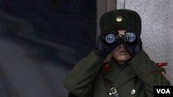 Seorang tentara Korut menggunakan teropong untuk melihat wilayah perbatasan di Panmunjom (dokumentasi).