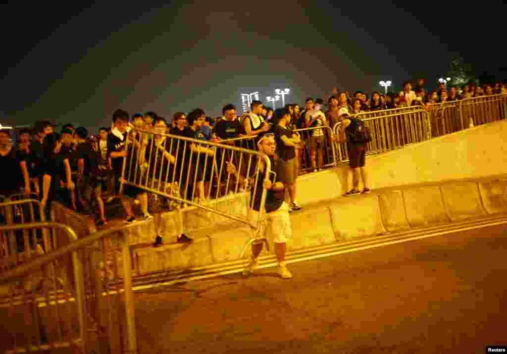 Etirazçılar Honq Konq Baş İdarəçisi Leunq Çun-yinqin ofisinin qarşısındakı xiyabanı bağlamağa çalışırlar. 2 oktyabr, 2014.