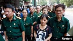 A woman holds a portrait of General Giap outside the National Funeral House in Hanoi, Oct. 12, 2013.